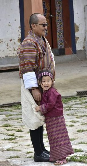 Happy Bhutanese father and daughter, both wearing traditional dress.