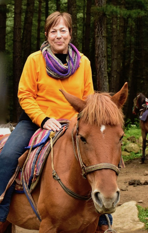 Cynthia Samake riding to the Tiger's Nest Monastery on sorrel horse, in Bhutan.