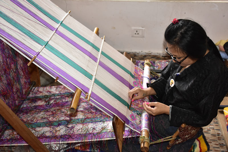 Bhutan weaver working at a slanted loom.