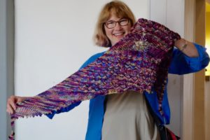Knitter holds up her lovely lace shawl from BTSA knitting retreat.