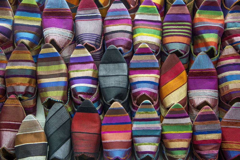 Brightly colored striped shoes stacked in the market.