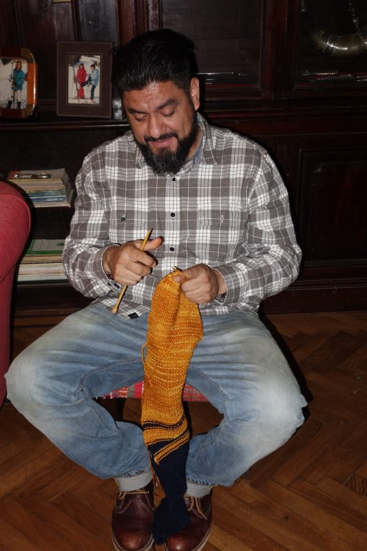 Gerardo sitting in a chair knitting on gold yarn to make a muffler.