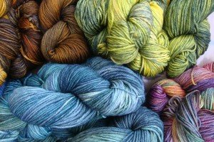 Pile of hand-dyed yarns in blue and green hues.