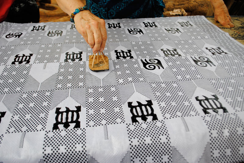 Printing Adinkra cloth with traditional gourd stamps.