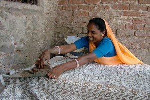 Woman leans over cloth to stamp the far edge; INDIA