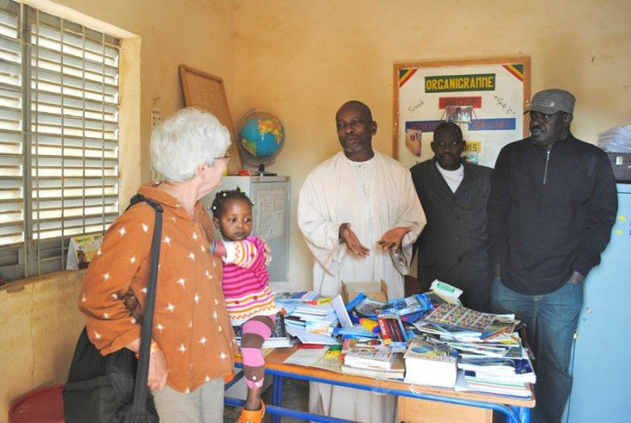 Director in Segou receives BTSA travelers' donations to the school.