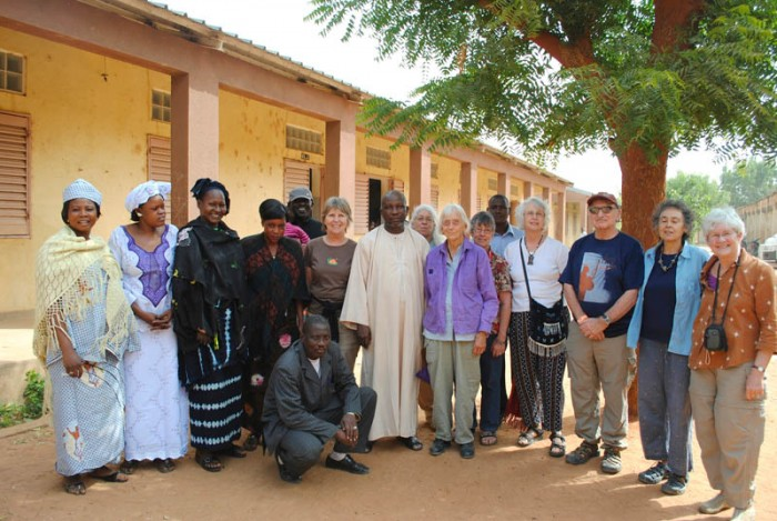 Staff of Segou school and BTSA travelers pose next to the classrooms in the bare schoolyard.