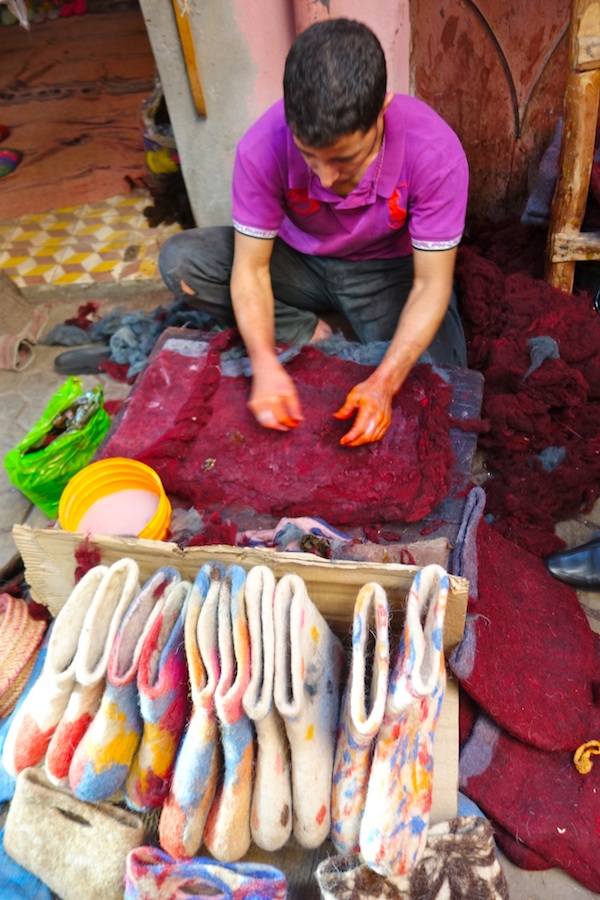Man uses friction and soap/water to felt sheep's wool at the Fes craft market.