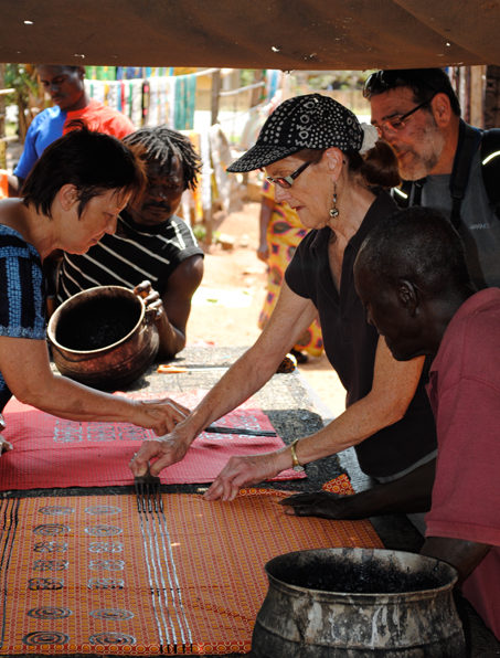 Jean and Cynthia decorate cloth with Adinkra designs.