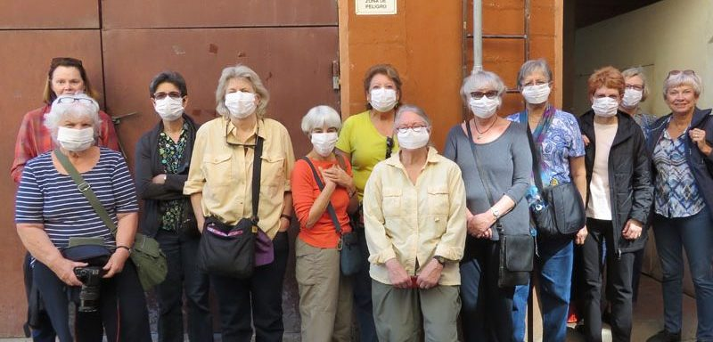 Group of women with white masks wait to tour a hat factory in Sucre.