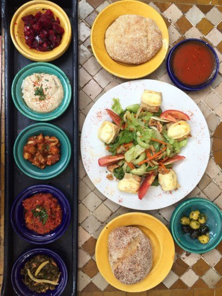 Variety of Moroccan cooked mezze vegetable dishes with goat cheese salad and fresh bread; Casablanca restaurant.