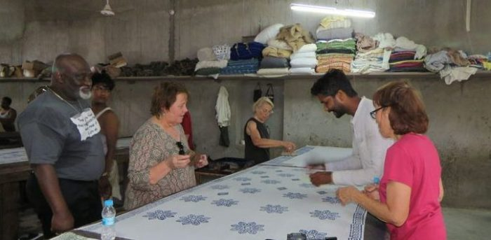 Textile group uses wooden block prints to stamp designs on white scarves, Bagru.