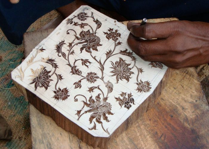 Artist using small chisel to cut flowers into wood block for printing.