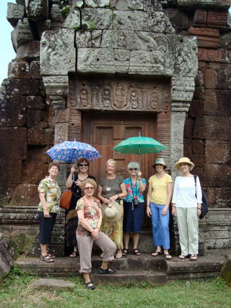 Travelers at Wat Phou Champasak in front of a Khmer monument.