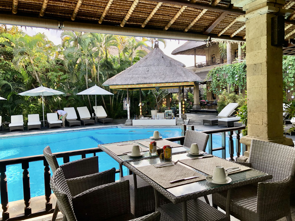 Swimming pool next to restaurant tables, Denpasar, Bali.