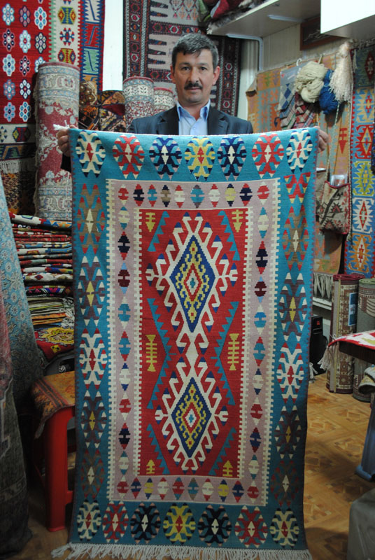 Rug vendor holds up a handmade blue carpet.