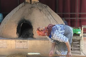 Moroccan baker slides another loaf into the wood-fired oven.