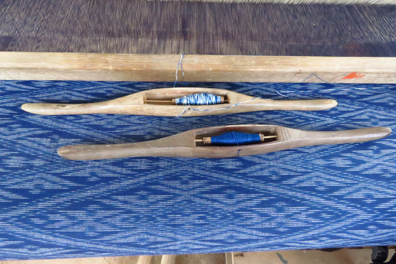 Indigo blue weft ikat weaving with bobbins on loom.