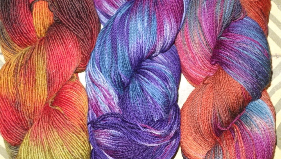 Three skeins of hand-dyed yarn.