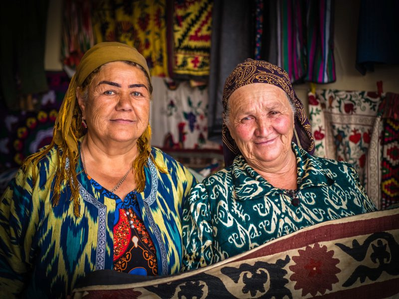 Two smiling women hold up a suzani textile.