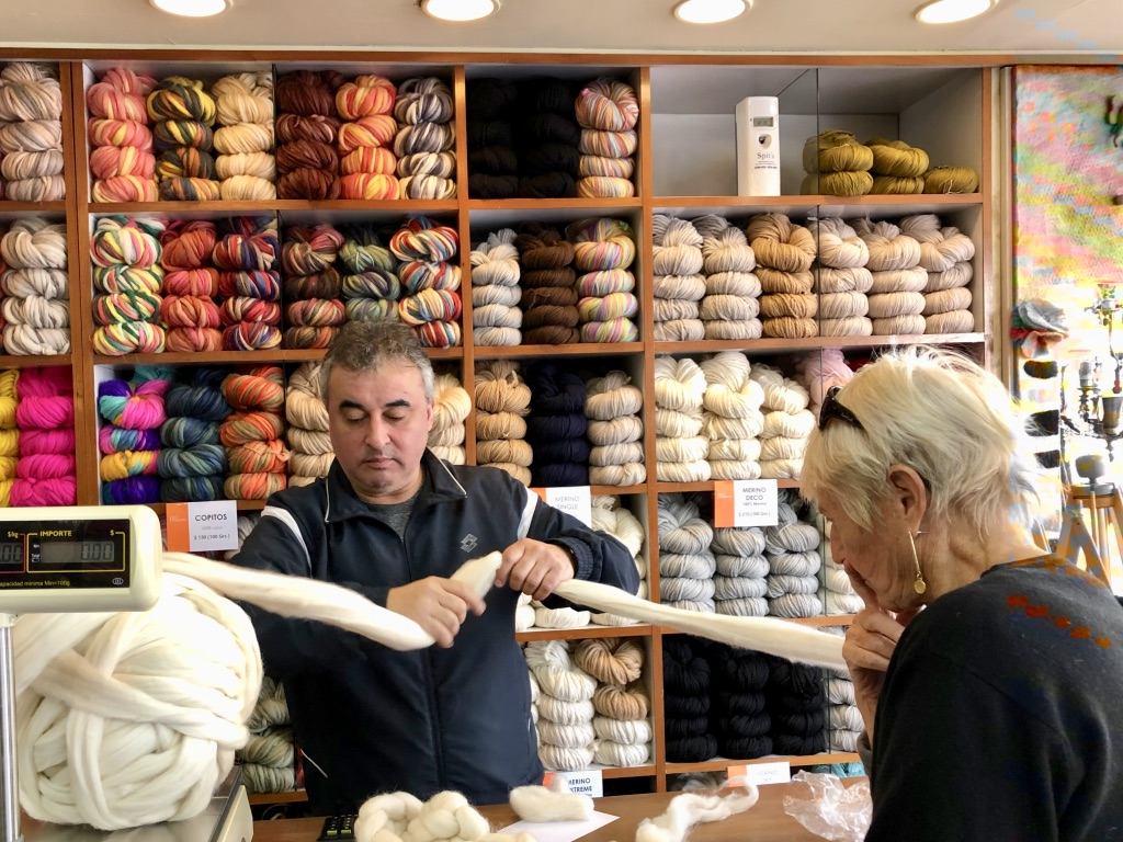 Woman buys woolen roving in a yarn store, Argentina