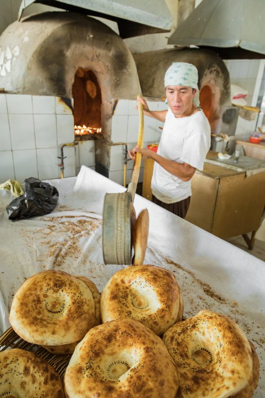 Man taking bread out of oven.