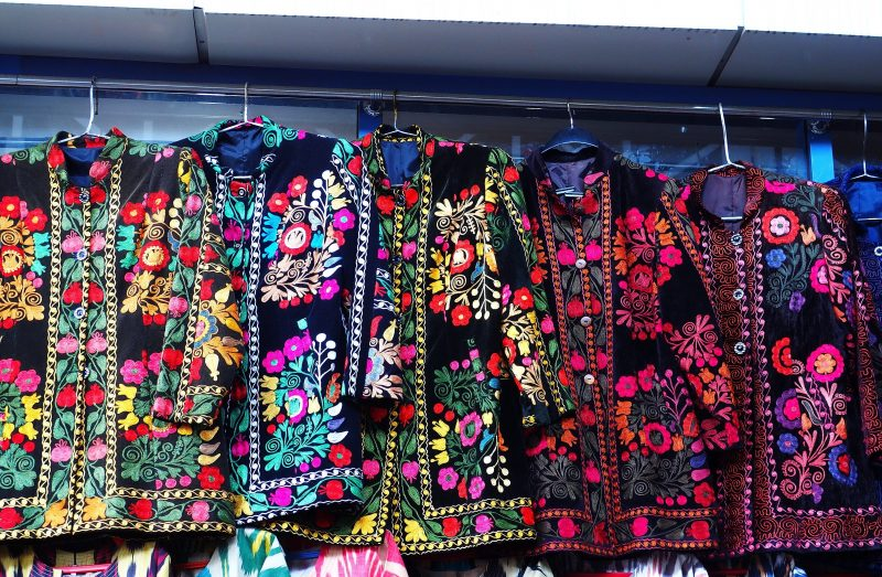 Five embroidered jackets hanging in market.