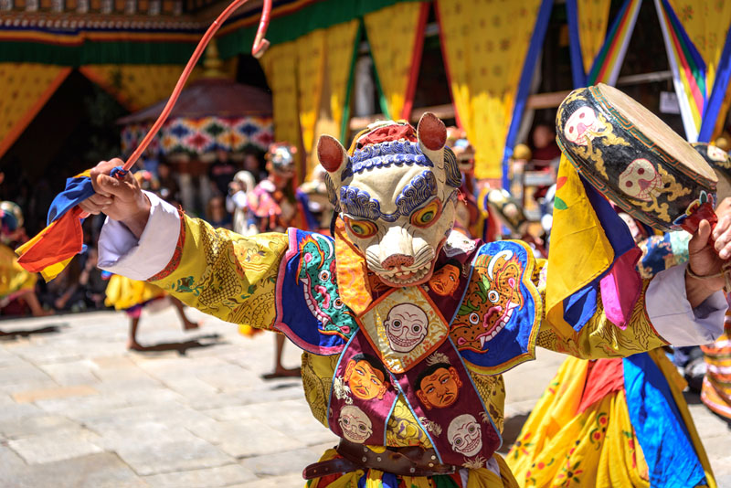 Bhutan Tsechu festival dancer with wooden mask salutes the crowd.