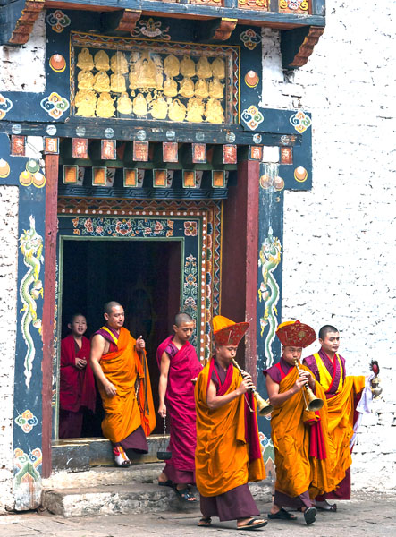 Monks playing horns in a festival, wearing orange robes in Trashigang, Bhutan.
