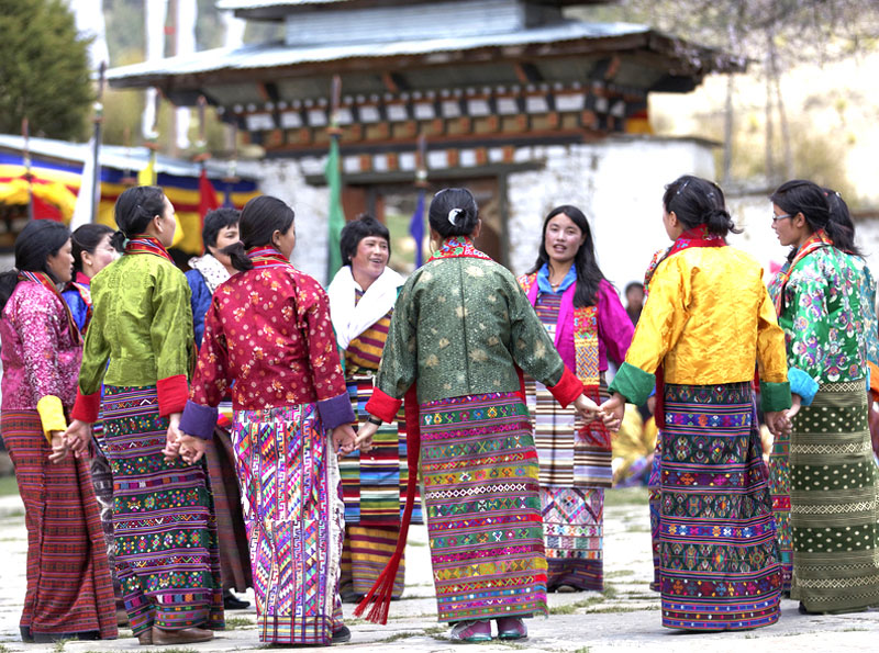 Women dance at a festival in Bhutan, wearing traditional weaving in the form of skirts.